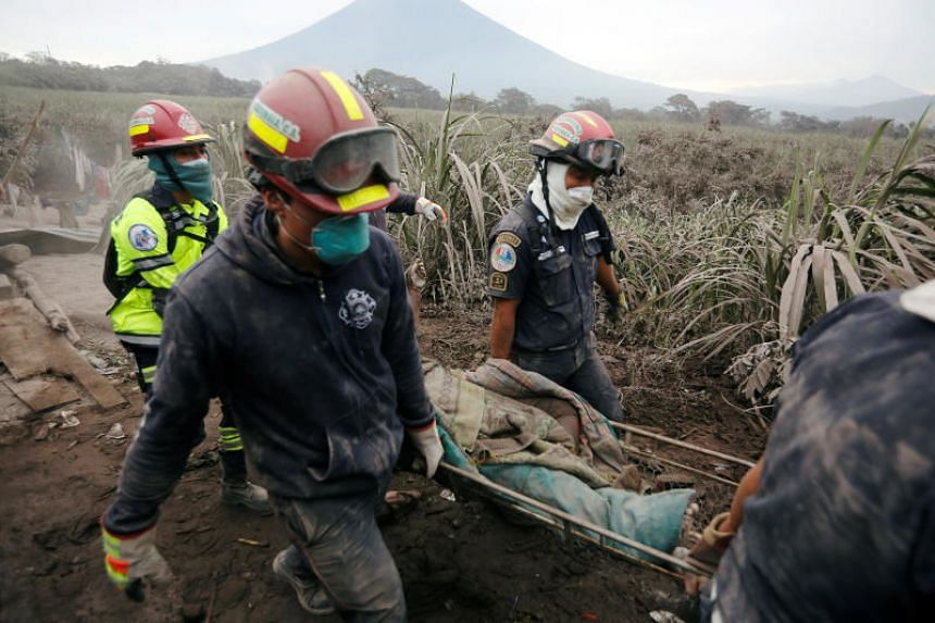 Firefighters carry a body at an area affected by the eruption of the Fuego volcano in the community of San Miguel Los Lotes in Escuintla, Guatemala, on June 4, 2018.