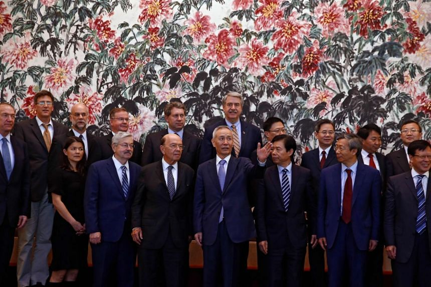 US Commerce Secretary Wilbur Ross chats with Chinese Vice Premier Liu He during a photograph session after their meeting at the Diaoyutai State Guesthouse in Beijing.