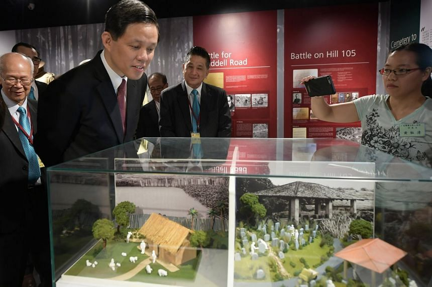 Minister for Trade and Industry Chan Chun Sing checking out miniature displays of past scenes at the opening of the Kwong Wai Siew Peck San Theng Heritage Gallery yesterday.