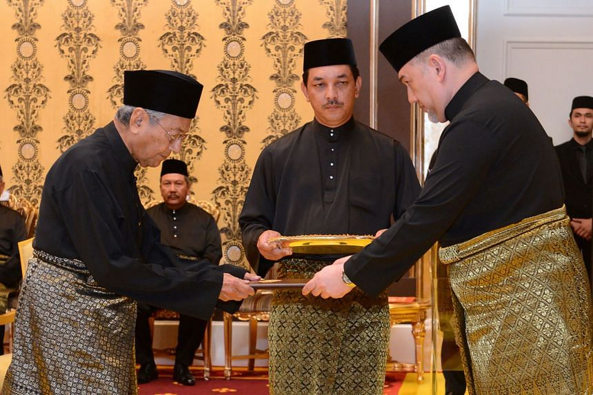 Malaysian Prime Minister Mahathir Mohamad (left) receiving the documents from King Muhammad V before taking the oath of office as the country's new Prime Minister in Kuala Lumpur last month.