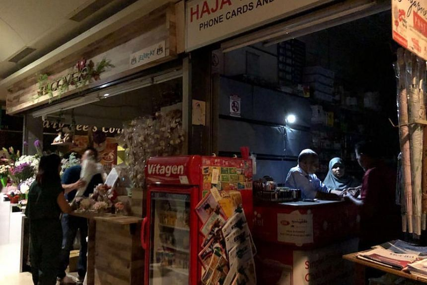 Shop owners working in the dark at The Arcade in Raffles Place, on June 1, 2018.  SP Group said the blackout was caused by maintenance work at a substation.