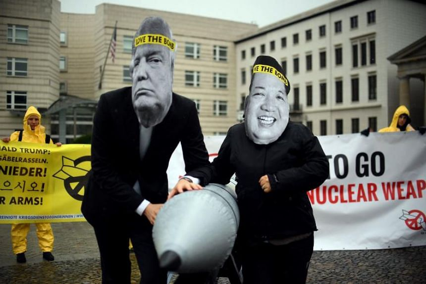 Activists of the International Campaign to Abolish Nuclear Weapons wearing masks of US President Donald Trump and North Korean leader Kim Jong Un while posing with a mock missile in front of the North Korean embassy in Berlin on Sept 13, 2017.
