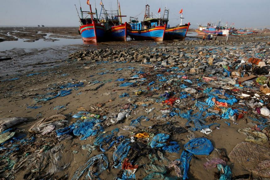 Fishermen boats are seen at a beach covered with plastic waste in Thanh Hoa province, Vietnam, on June 4, 2018.