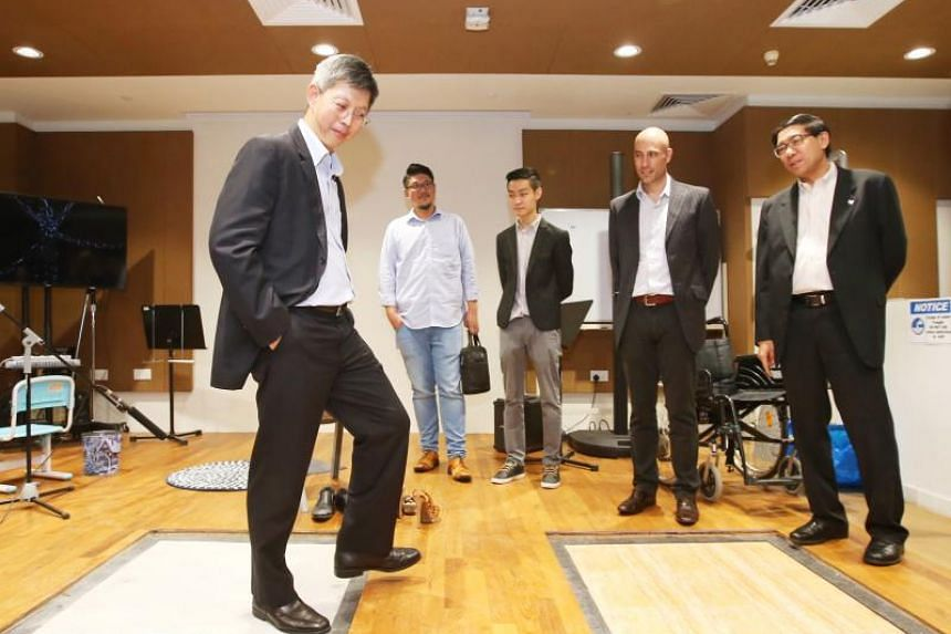 Republic Polytechnic deputy principal for academic services, Dr Michael Koh (left), stomping on different types of flooring in the Foley Arts Studio, while Republic Polytechnic principal and chief executive Yeo Li Pheow (right) and Ubisoft Singapore