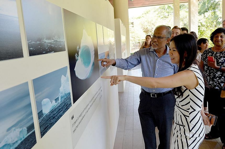 """An exhibition to inspire change: Minister for the Environment and Water Resources Masagos Zulkifli at the opening of """"Changing Course"""", a film and photography exhibition which tells stories about the impacts of climate change. With him is Jessica Che"""