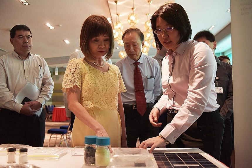 Singapore Polytechnic research scientist Thong Ya Xuan (right) showing Dr Amy Khor, Senior Minister of State for the Environment and Water Resources, a new development that can help the recycling and waste management industry at the poly yesterday.