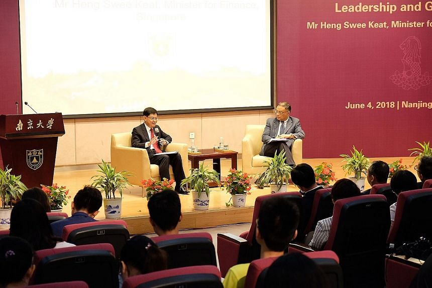 Finance Minister Heng Swee Keat engaging with Nanjing University students yesterday as dialogue moderator, Professor Zhu Feng of the university's Institute of International Studies, looks on. Mr Heng is on a nine-day working visit to China with stops
