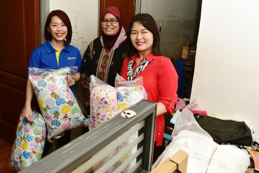 Courts Singapore marketing director Joanna Ho and Adviser to Aljunied GRC Grassroots Organisations Chan Hui Yuh with Madam Siti Norbayah Ahmad Sanaip, a stay-at-home mum who has four children.