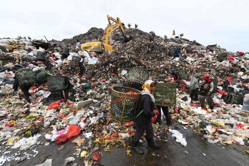 This picture taken on May 23, 2018 shows rubbish pickers sifting through a mountain of garbage at the Bantar Gebang landfill in the city of Bekasi, located on the outskirts of Jakarta. About eight million tonnes of plastic waste are dumped into the