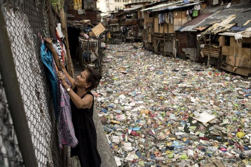 This photo taken on May 12, 2018 shows Perigrina Santos, 81, collecting her laundry next to a garbage-filled creek in Manila. The blanket of trash on a creek that flows between the makeshift homes of a Manila slum is so dense it appears one could wa