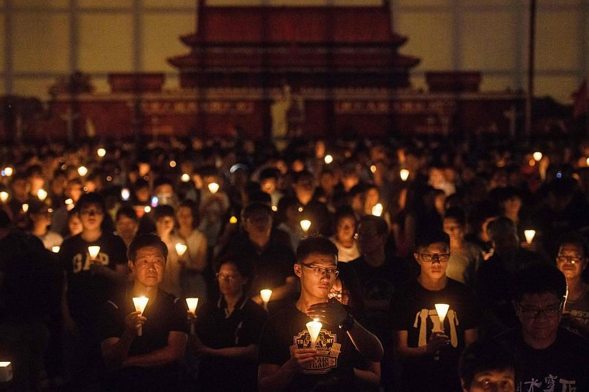 People hold candles during a vigil in Hong Kong, on June 4, 2018, to mark the 29th anniversary of the 1989 Tiananmen crackdown in Beijing.