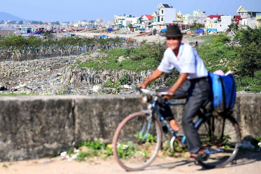 This picture taken on May 15, 2018 shows a man riding his bicycle past plastic waste washed up along the coast in Thanh Hoa province, around 150 km south of Hanoi. About eight million tonnes of plastic waste are dumped into the world's oceans every