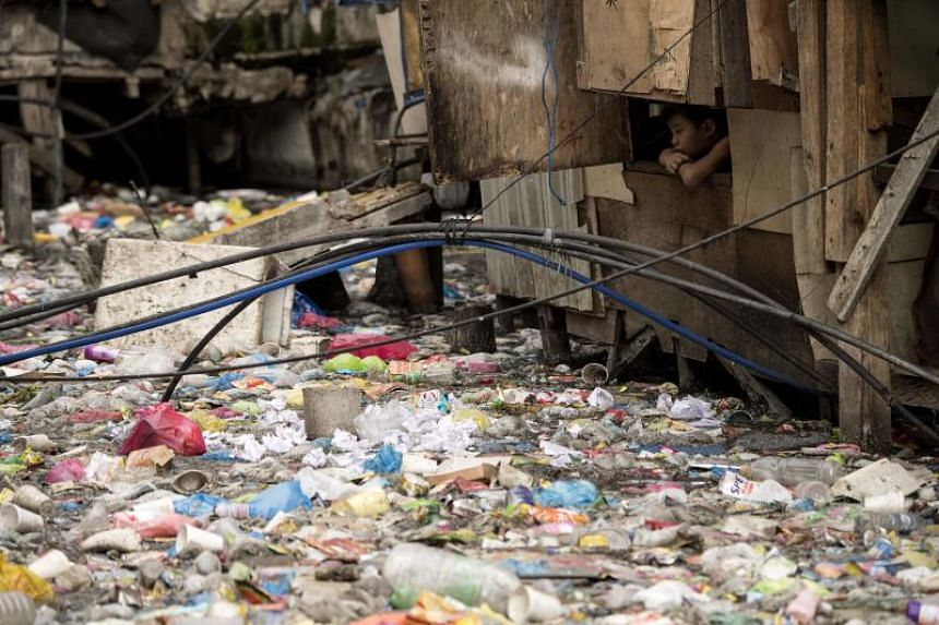 The blanket of trash on a creek that flows between the makeshift homes of a Manila slum is so dense it appears one could walk across it like a paved street.