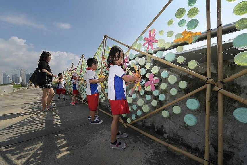 Pupils from PCF Sparkletots @ Zhenghua putting the finishing touches to a 120m caterpillar made of discarded plastic bottles at Marina Barrage. The art installation, which aims to raise awareness about plastic pollution, will be on display for a mont