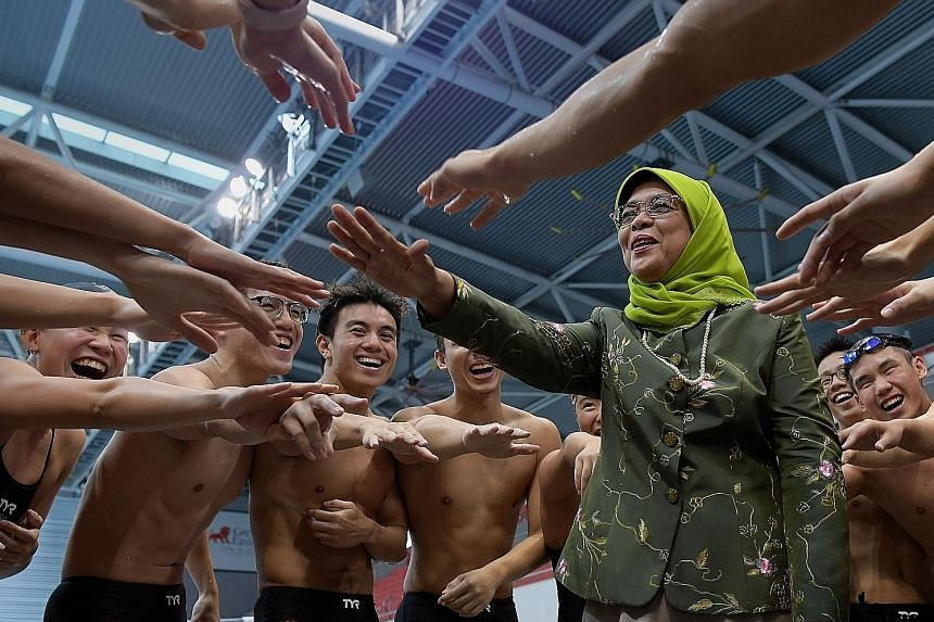 President Halimah Yacob taking part in a cheer with Team Singapore swimmers at the OCBC Aquatic Centre yesterday. President Halimah paid a visit to Team Singapore athletes from swimming - including Olympic champion Joseph Schooling - boccia, pencak s