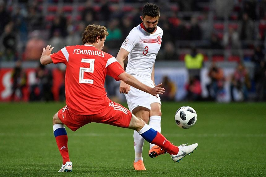 Russia's Mario Fernandes (left) and Turkey's Hasan Ali Kaldirim vie for the ball during an international friendly football match between Russia and Turkey at Moscow's VEB Arena on June 5, 2018.