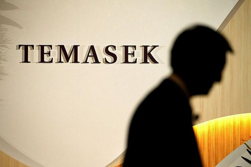 File photo showing a man walking past a Temasek logo at one the company's offices.