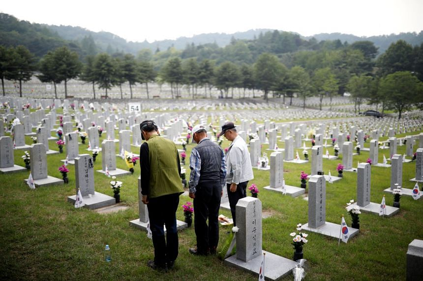 People paying their respects to a relative who died for the country at the national cemetery in Seoul yesterday, on the eve of South Korea's Memorial Day. Seoul's presidential Blue House said yesterday that South Korea will continue to seek a formal