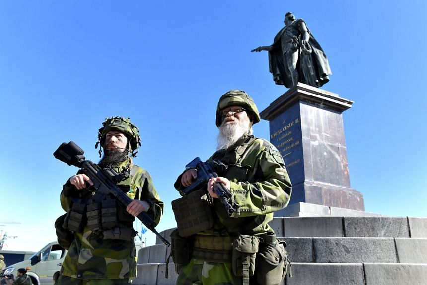 Reservist soldiers Konrad Lindblad and Par Thorhard stand guard outside the Stockholm Palace during a military exercise.