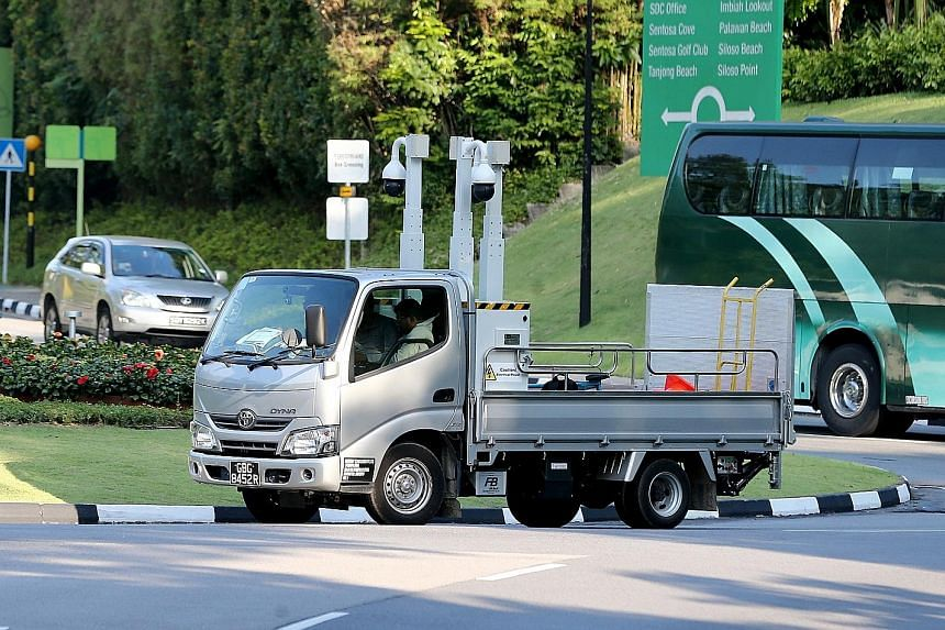 Additional security cameras were seen being put up on Sentosa ahead of the summit. A queue of cars (above) in Sentosa Cove yesterday amid heightened security. At Capella hotel (right), security staff were stationed at the entrance to screen visitors.