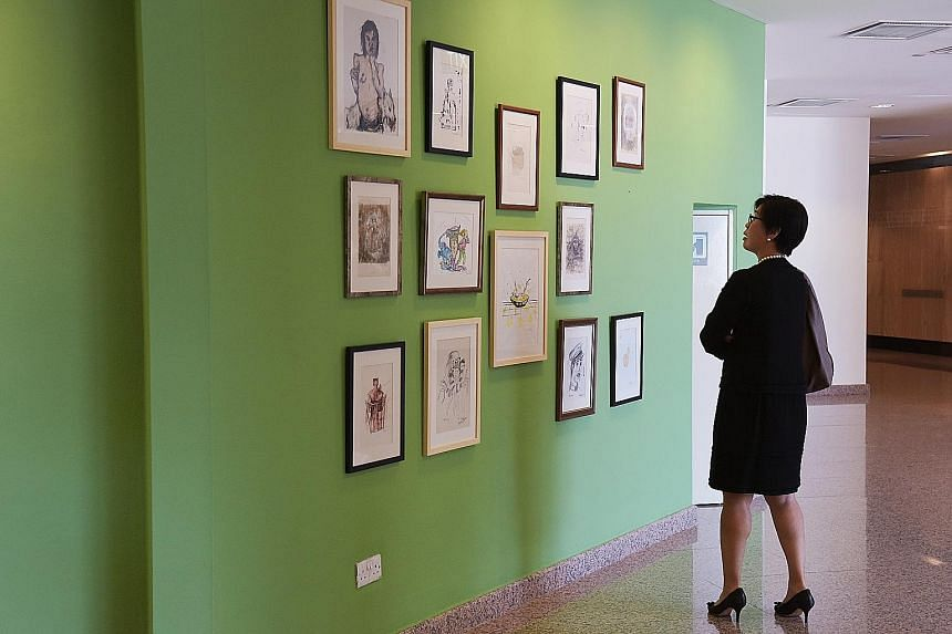 A visitor to the Esplanade looking at the artworks on the wall where Vincent Leow's controversial piece had been displayed, now an empty space between the two drawings at the extreme right of the wall.