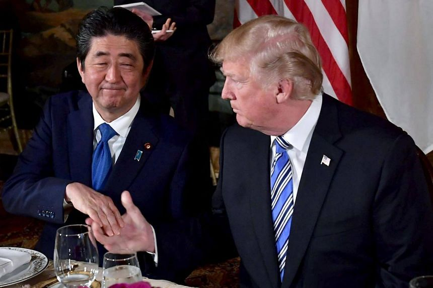 Japanese Prime Minister Shinzo Abe (left) shakes hands with US President Donald Trump during a dinner at Trump's Mar-a-Lago estate in Palm Beach, Florida, on April 18, 2018.