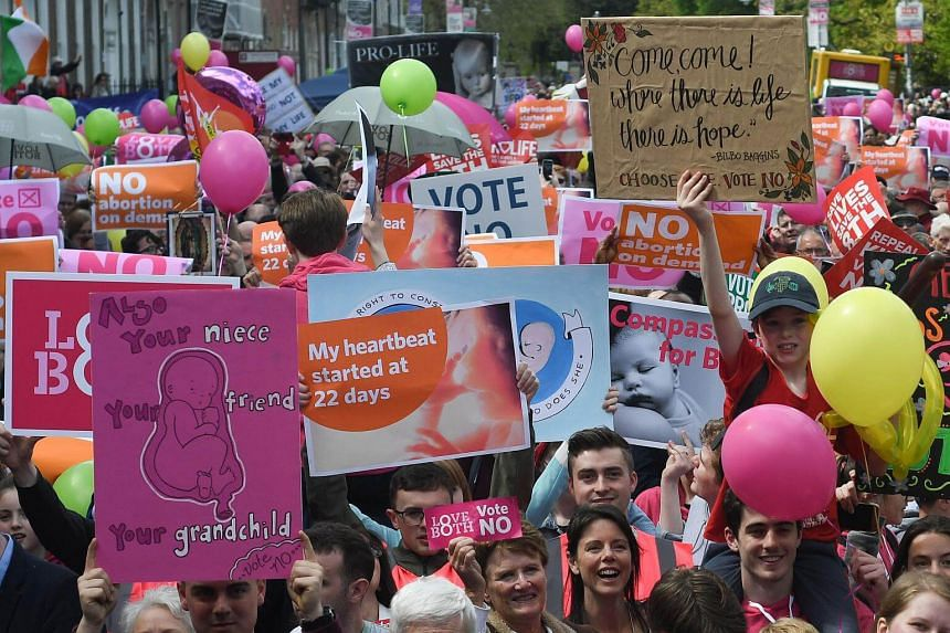 """People hold up placards during a """"Stand up for Life"""" rally in Dublin, on May 12, 2018."""