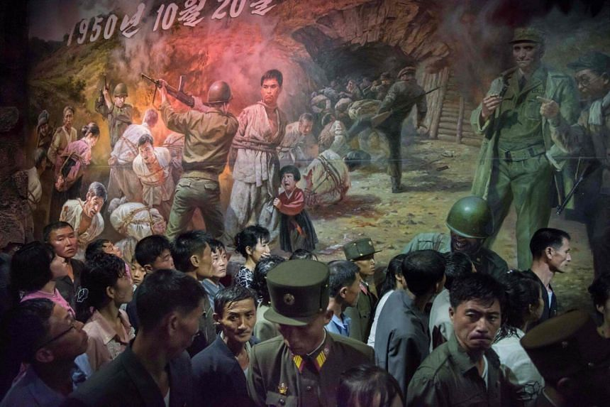 North Korean visitors walking past a painting showing US soldiers preparing to kill people at the Sinchon Museum of American War Atrocities in Sinchon, south of Pyongyang.