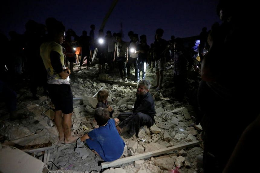 People at the site of a car bomb attack in Sadr City district of Baghdad, Iraq, on June 6, 2018.