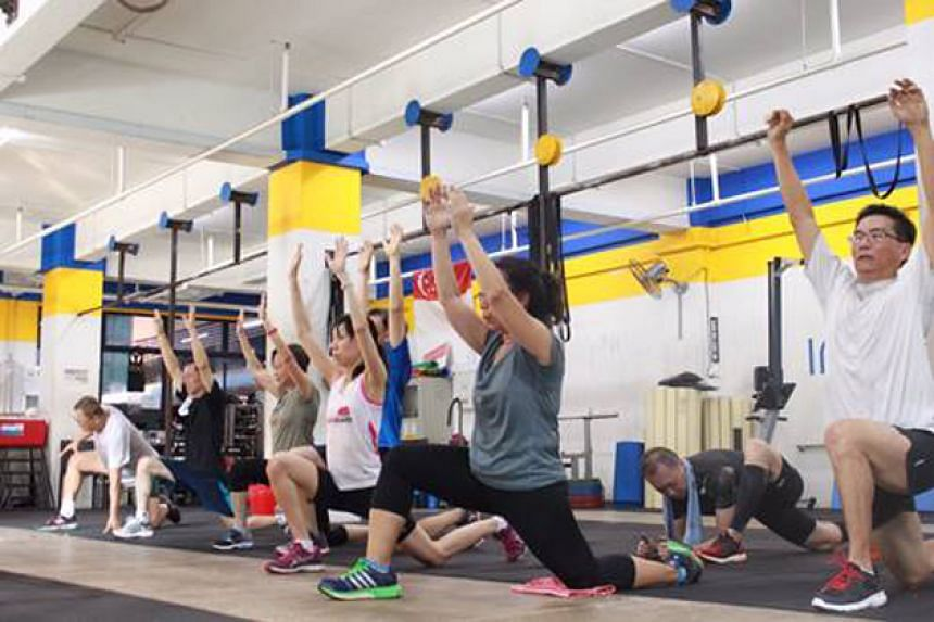 Participants focusing on bodyweight exercises like squats and lunges during a CrossFit class at Innervate Fitness.