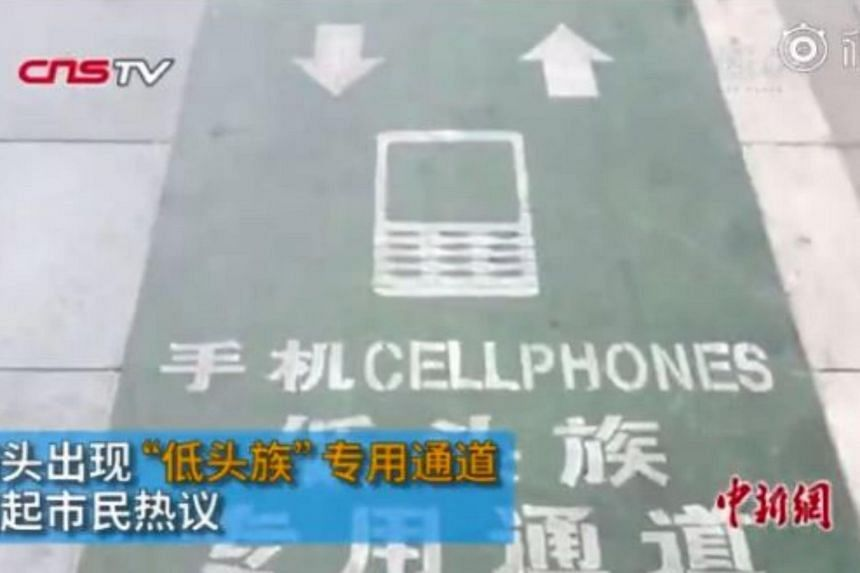 A dedicated path for mobile phone users has been introduced at the entrance of a shopping mall on Yan Da Road in Xi An.