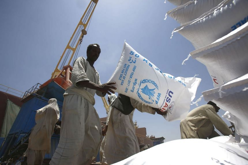 Sudanese dockers unload bags of sorgham (cereal) from one of two US ships carrying humanitarian aid supplies.