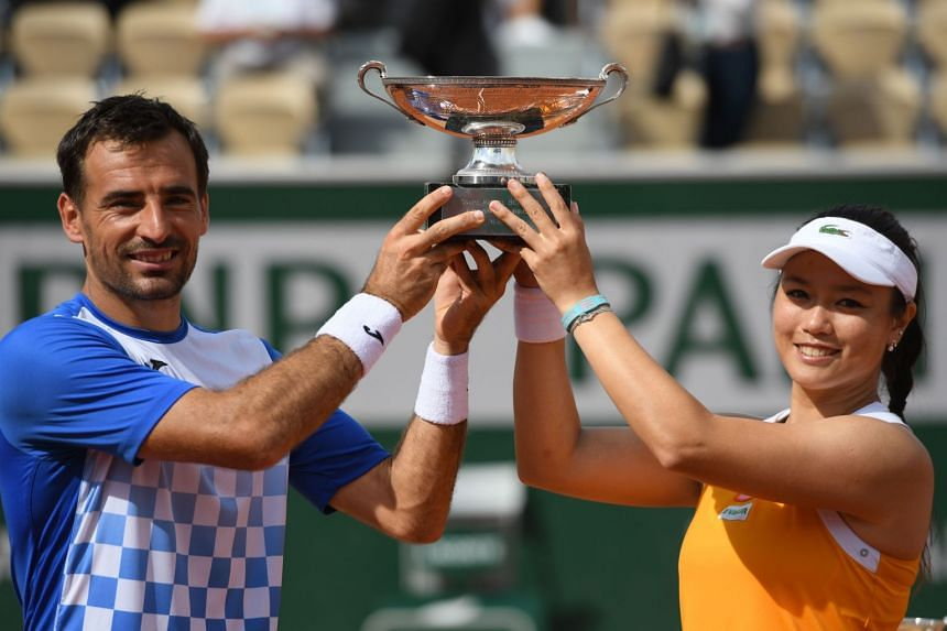 Taiwan's Latisha Chan and Croatia's Ivan Dodig pose with the trophy after their victory.