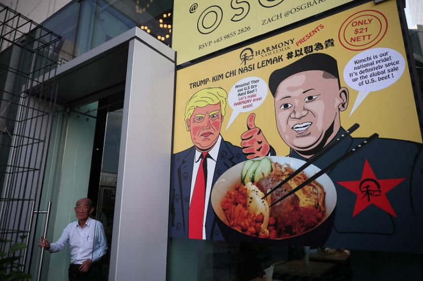 A poster depicting US President Donald Trump and North Korean leader Kim Jong Un with a promotional dish of Trump-Kim Chi Nasi Lemak at a restaurant in Singapore on June 6, 2018.
