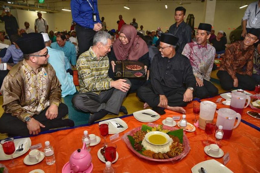 (From left)  Prime Minister Lee Hsien Loong, Minister-in-charge of Muslim Affairs Masagos Zulkifli and chief executive of Muis, Hj Abdul Razak Maricar, during the iftar at Masjid Maarof in Jurong West on June 7, 2018.