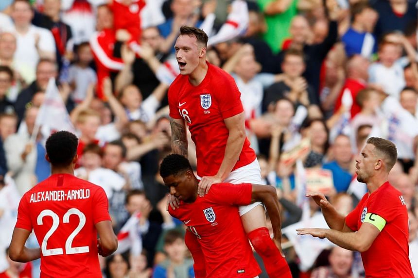 England's Marcus Rashford celebrates scoring their first goal with Phil Jones and team mates.