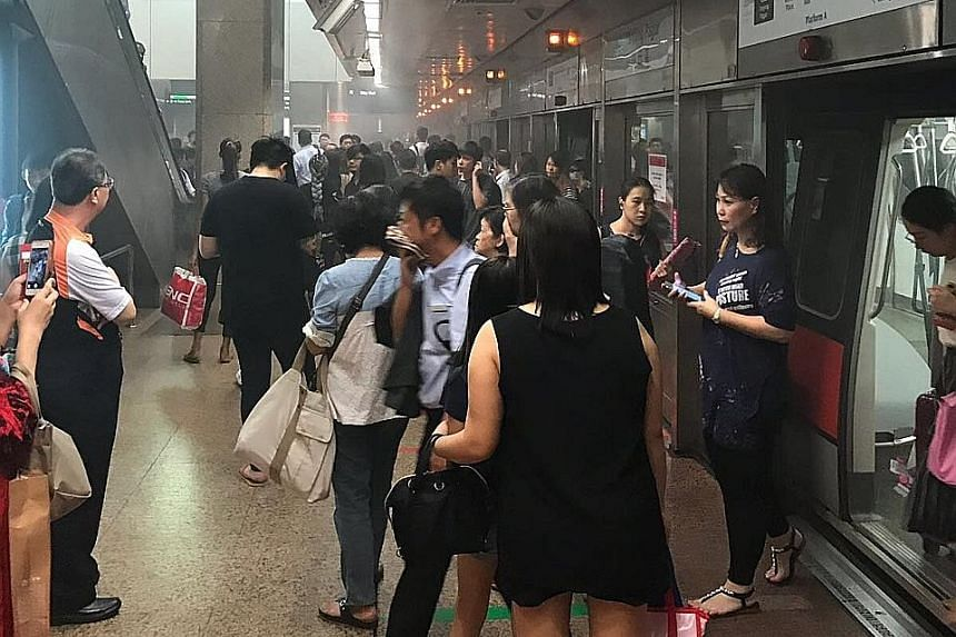Commuters on the smoky platform at Tanjong Pagar MRT station yesterday morning. The train with the leaking air-conditioning compressor was withdrawn from service for checks, said SMRT.