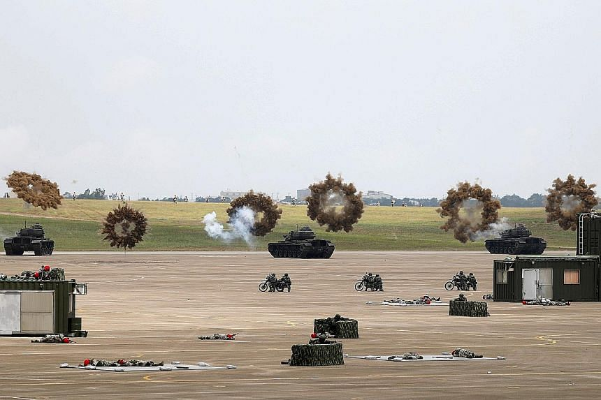 """Tanks firing smoke bombs during the """"Han Kuang"""" military exercise at the Ching Chuan Kang Air Base, in Taichung, Taiwan, yesterday. More than 4,000 personnel and over 1,500 pieces of equipment were deployed in the annual exercise."""