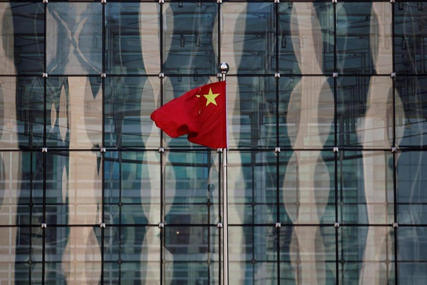A Chinese national flag flutters in front of a building on a financial street in central Beijing, China.