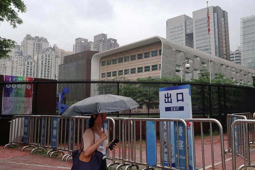 A woman shields herself from the rain as she walks past the US Consulate in Guangzhou, China, on June 7, 2018.