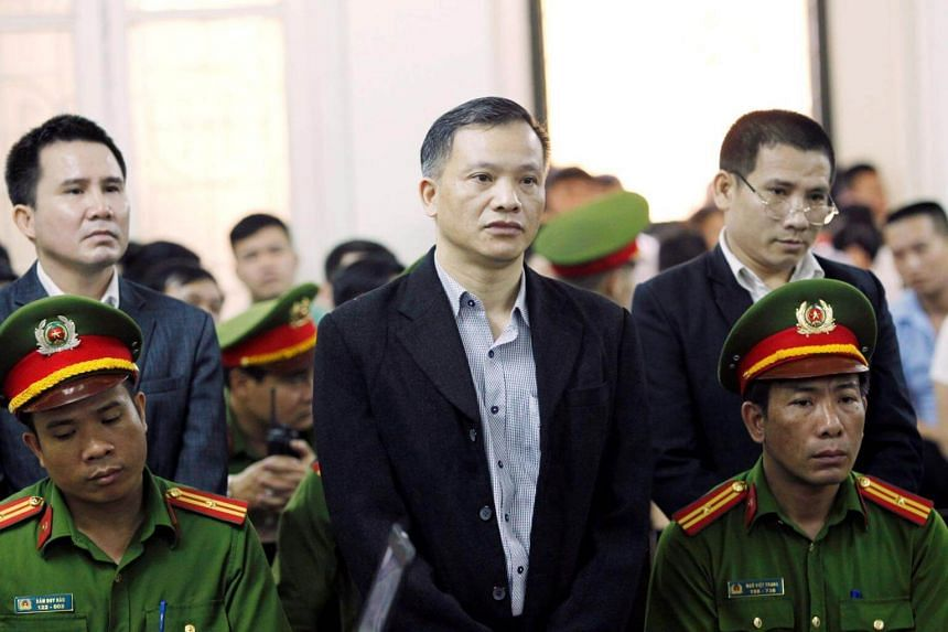Vietnamese dissident Nguyen Van Dai (centre), founder of the anti-government Brotherhood for Democracy group, stands at a court in Hanoi on April 5, 2018.