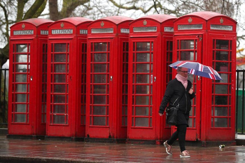 A woman walks past several traditional red telephone boxes in central London, Britain, on April 2, 2018.