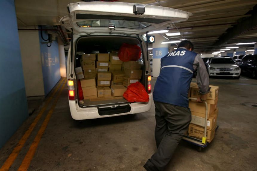 Inland Revenue Authority of Singapore (Iras) forensic officers unloading documents and other evidence from a van at Revenue House after a raid on a firm that Iras suspects is evading taxes.