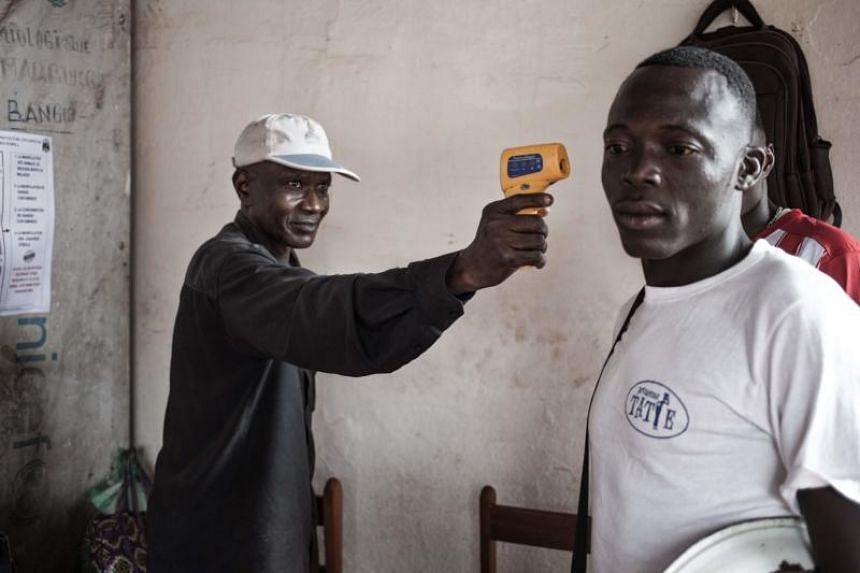 A health worker from the Ministry of Health monitors the temperature of a traveller from the Democratic Republic of Congo at each port in Bangui on June 3, 2018.