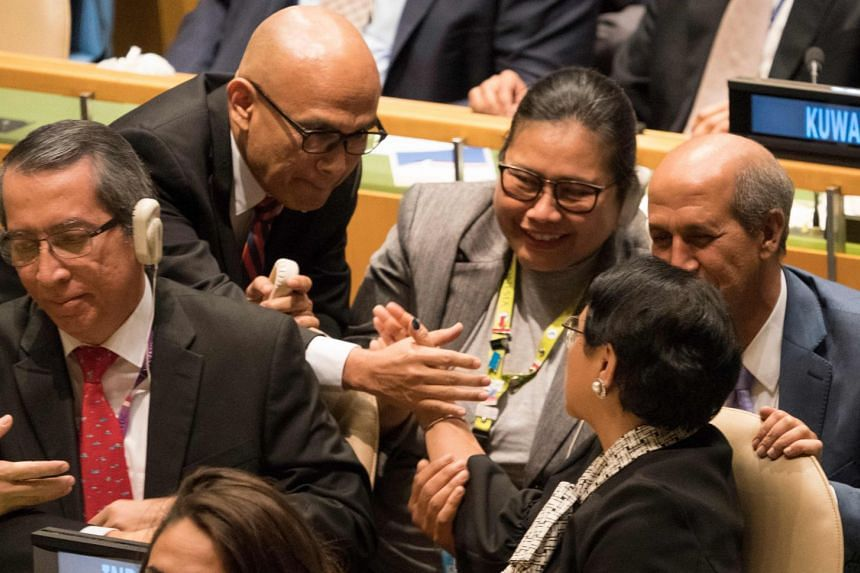 The delegation from Indonesia reacts after the vote at the United Nations in New York.