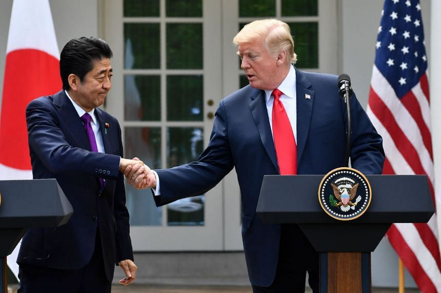 Trump and Abe shake hands during a joint press conference in the Rose Garden of the White House.