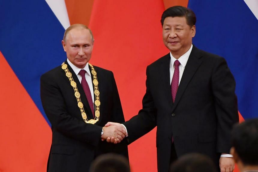 Chinese President Xi Jinping congratulating Russian President Vladimir Putin after presenting him with the Friendship Medal in the Great Hall of the People in Beijing on June 8, 2018.