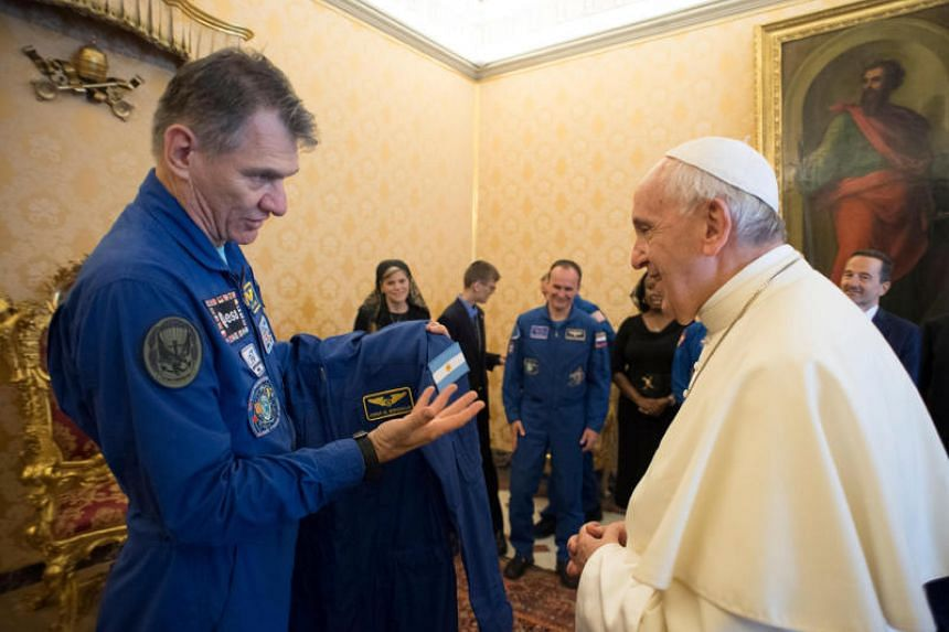 Pope Francis receives his own blue jump suit  from Italian astronaut Paolo Nespoli during a private meeting with crew members of the ISS 53 space mission at the Vatican on June 8, 2018.