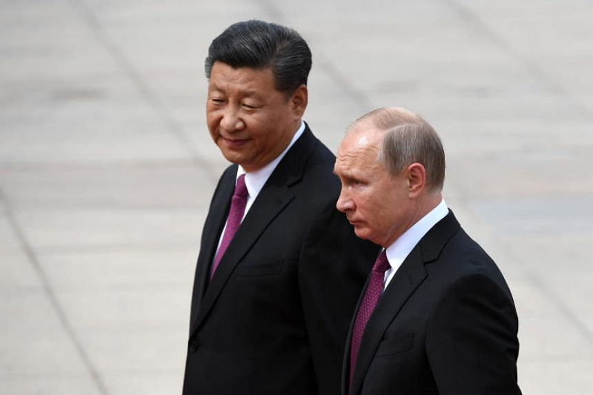 Russia's President Vladimir Putin reviewing a military honour guard with Chinese President Xi Jinping during a welcoming ceremony outside the Great Hall of the People in Beijing on June 8, 2018.
