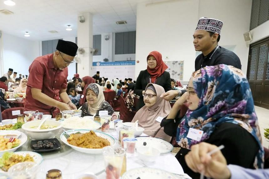 Minister-in-charge of Muslim Affairs Masagos Zulkifli (left) serving food during the Ramadan Disbursement Ceremony on June 8, 2018.